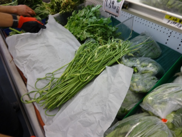 Our garlic scapes for sale in the neighborhood market.